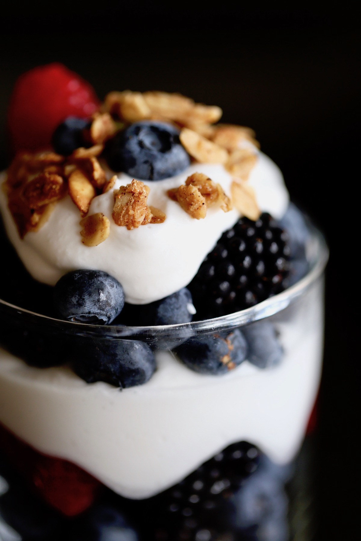 homemade coconut milk whipped cream gets layered with berries and granola for a delicious, healthy dessert