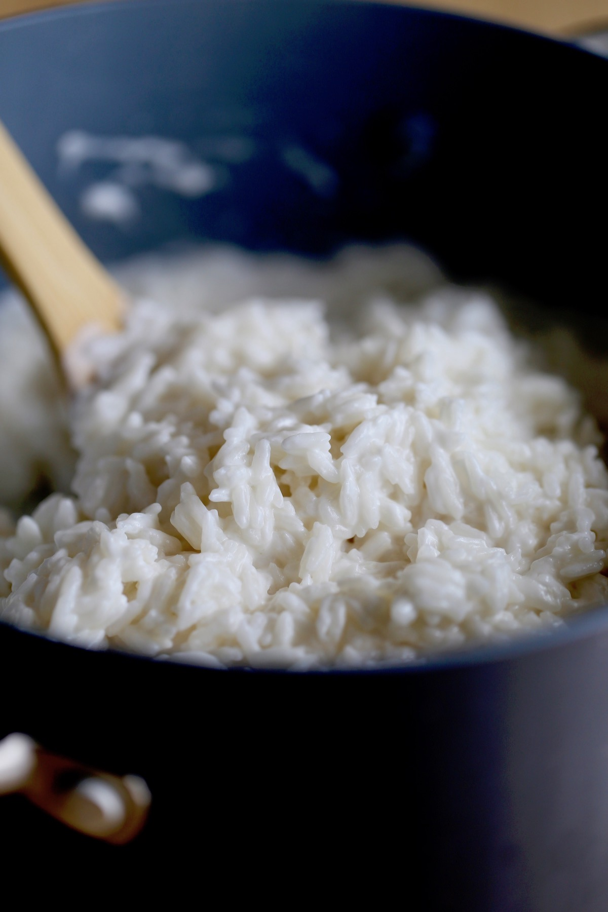 coconut rice being scooped up from a pot with a wooden spoon