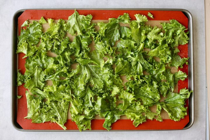 kale leaves coated in oil and salt on a baking sheet