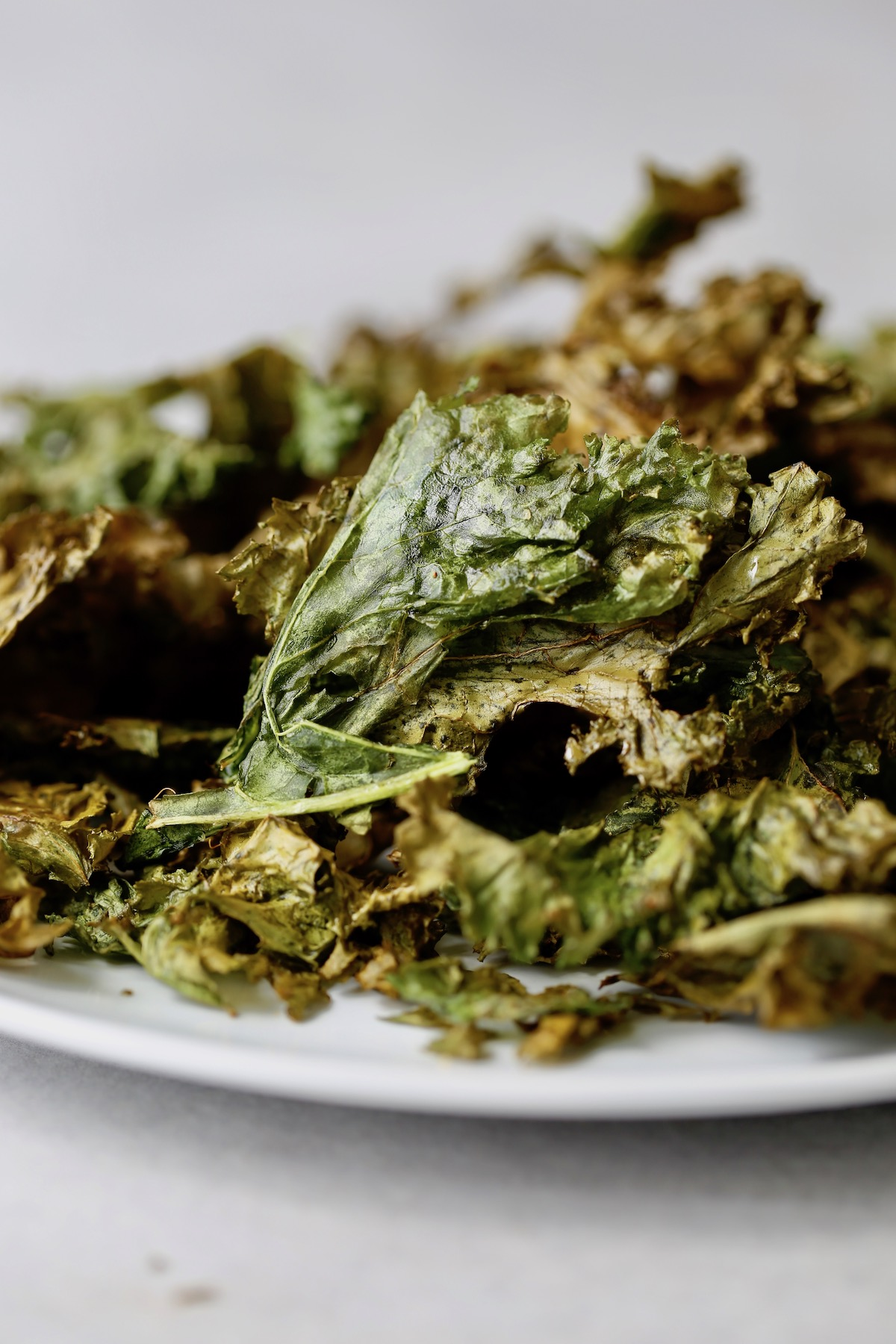 a plate piled high with homemade kale chips