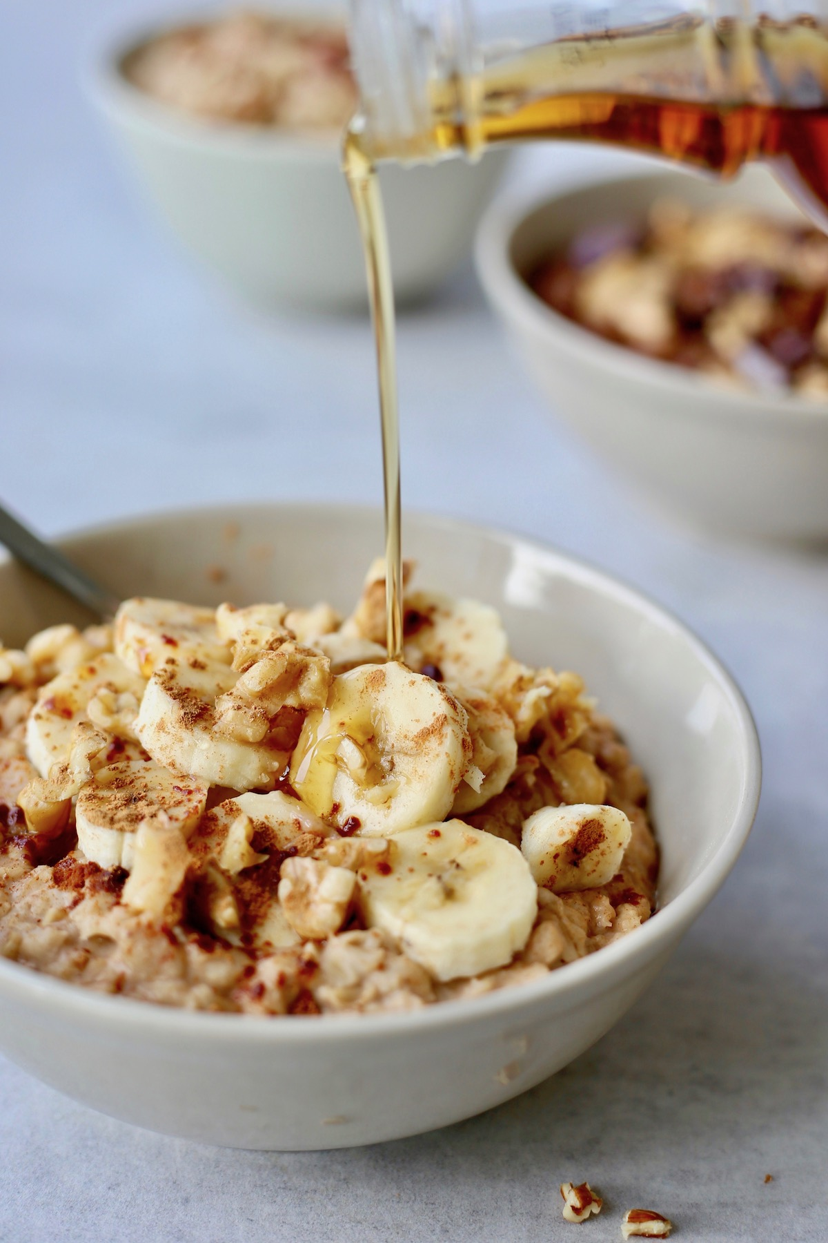 maple syrup being poured onto a bowl of banana oatmeal