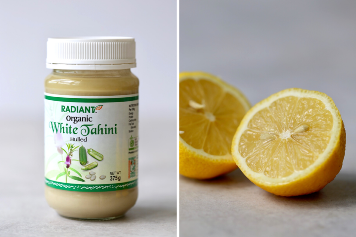 a jar of tahini and a cut lemon showing the main ingredients for lemon tahini dressing