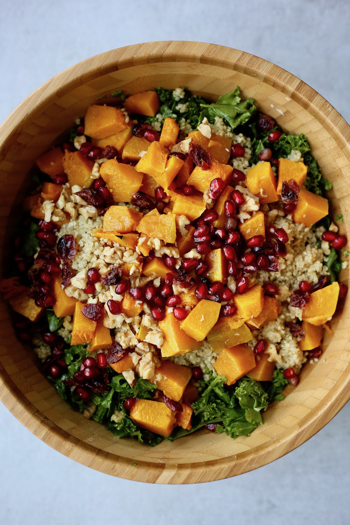 Massaged kale salad topped with quinoa, pomegranate arils, walnuts and roasted squash