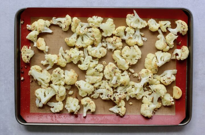 roasted cauliflower and garlic cloves on a baking sheet