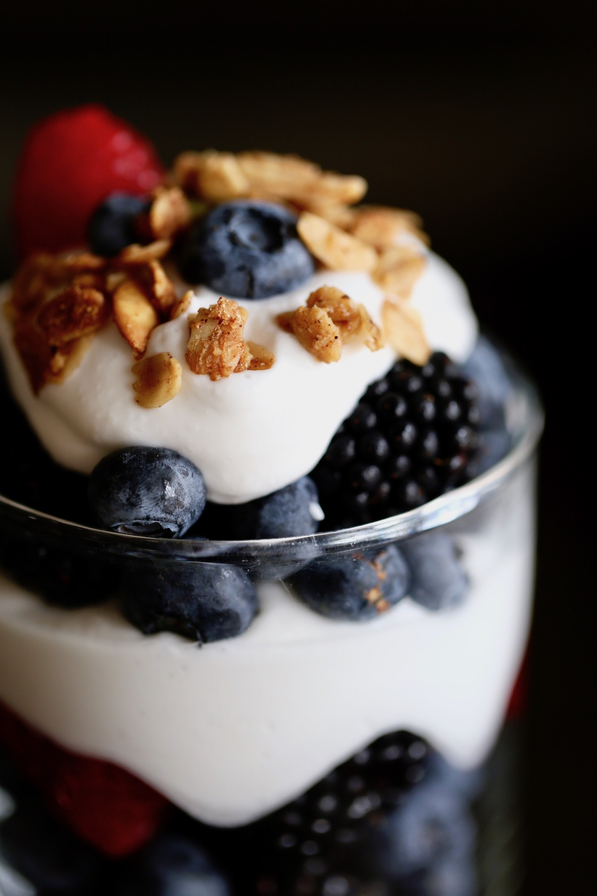 a close-up of granola and coconut milk whipped cream topping fresh berries in a glass jar