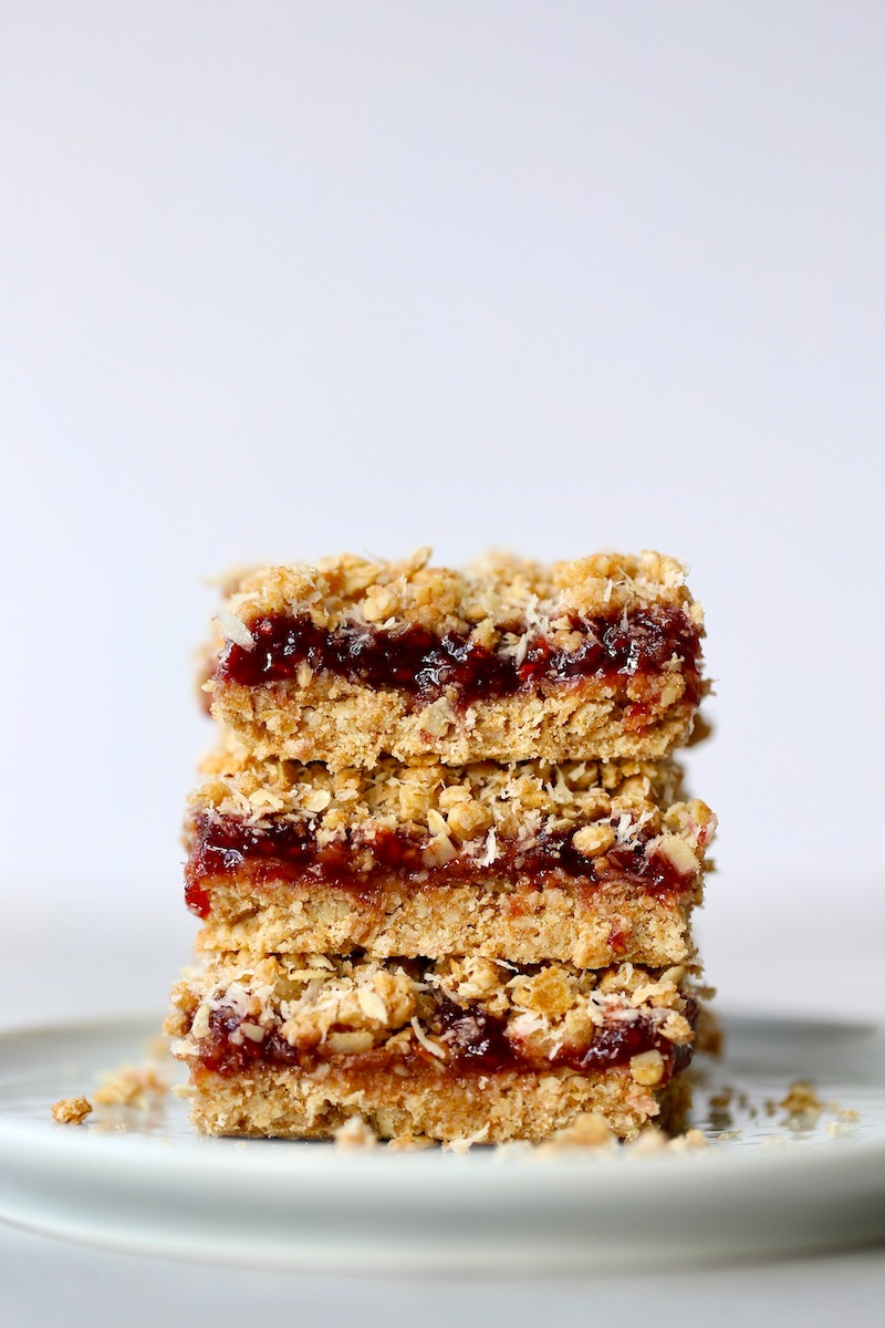 three crumbly vegan strawberry jam oatmeal bars stacked on a plate