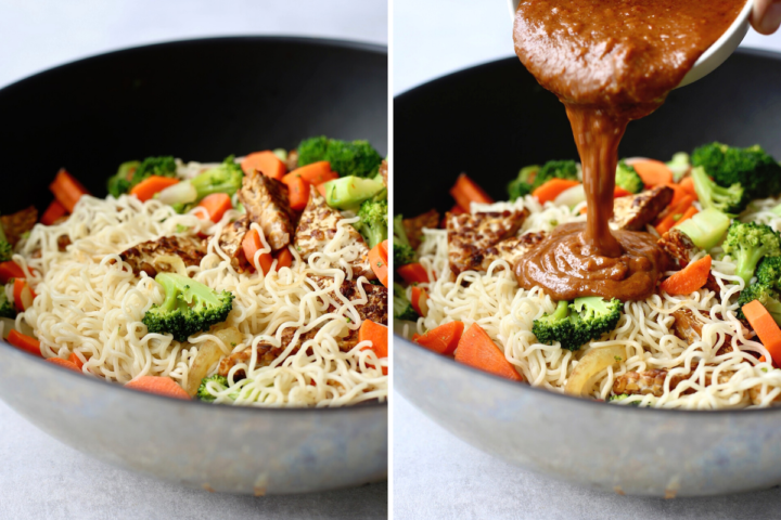 vegan almond butter sauce being poured over a wok full of noodles, veggies and tempeh
