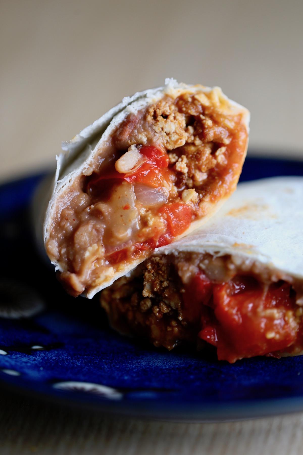 A vegan breakfast burrito cut in half on a plate