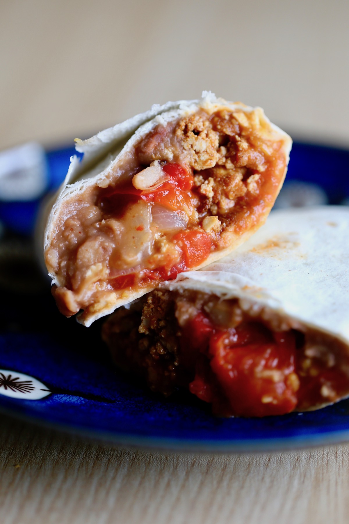 a vegan breakfast burrito stuffed with refried beans, salsa and taco tofu