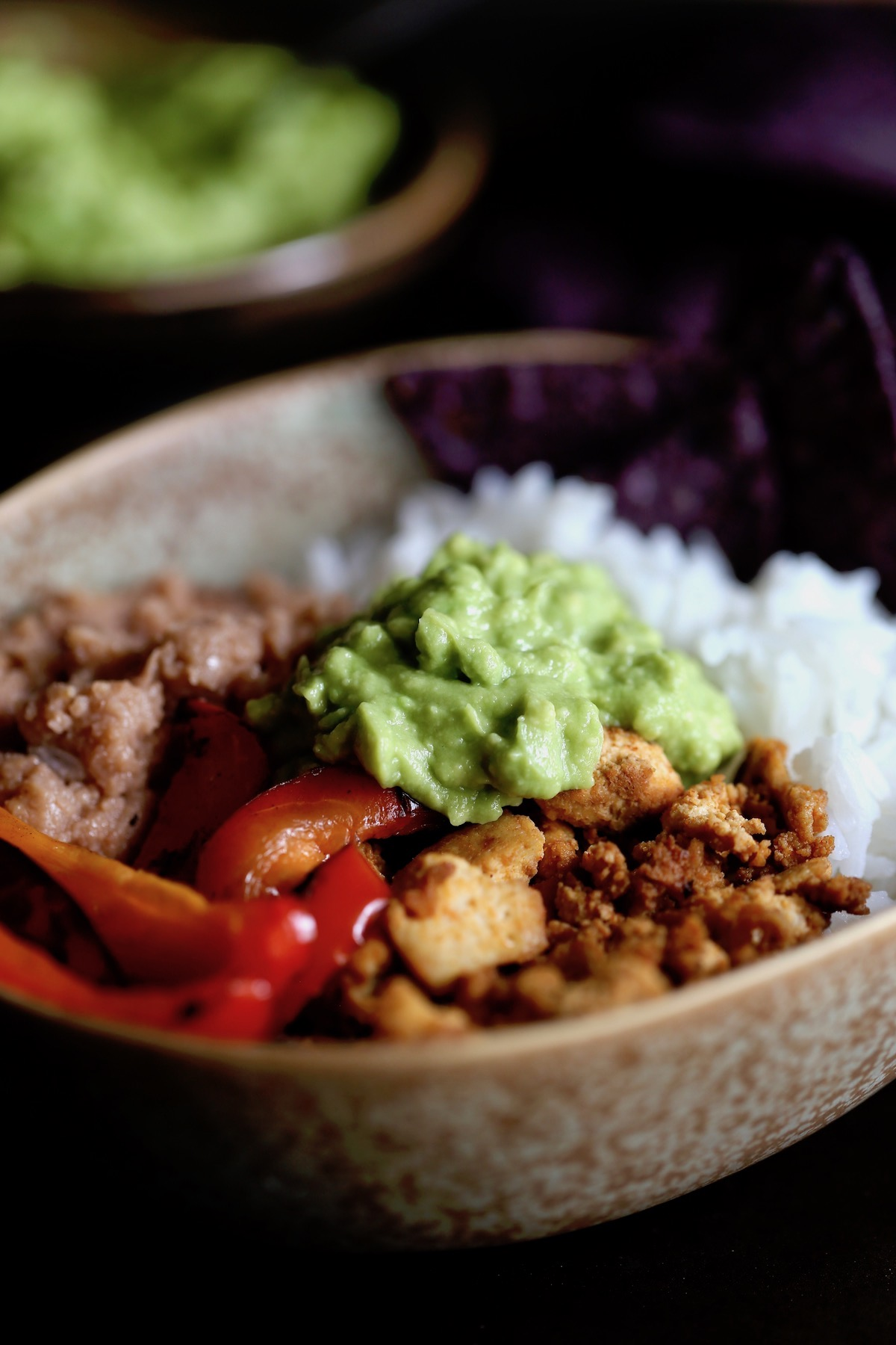 a vegan burrito bowl loaded with white rice, refried beans, taco tofu crumbles, sauteed peppers and homemade guac