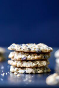 four vegan ranger cookies stacked high on a baking sheet