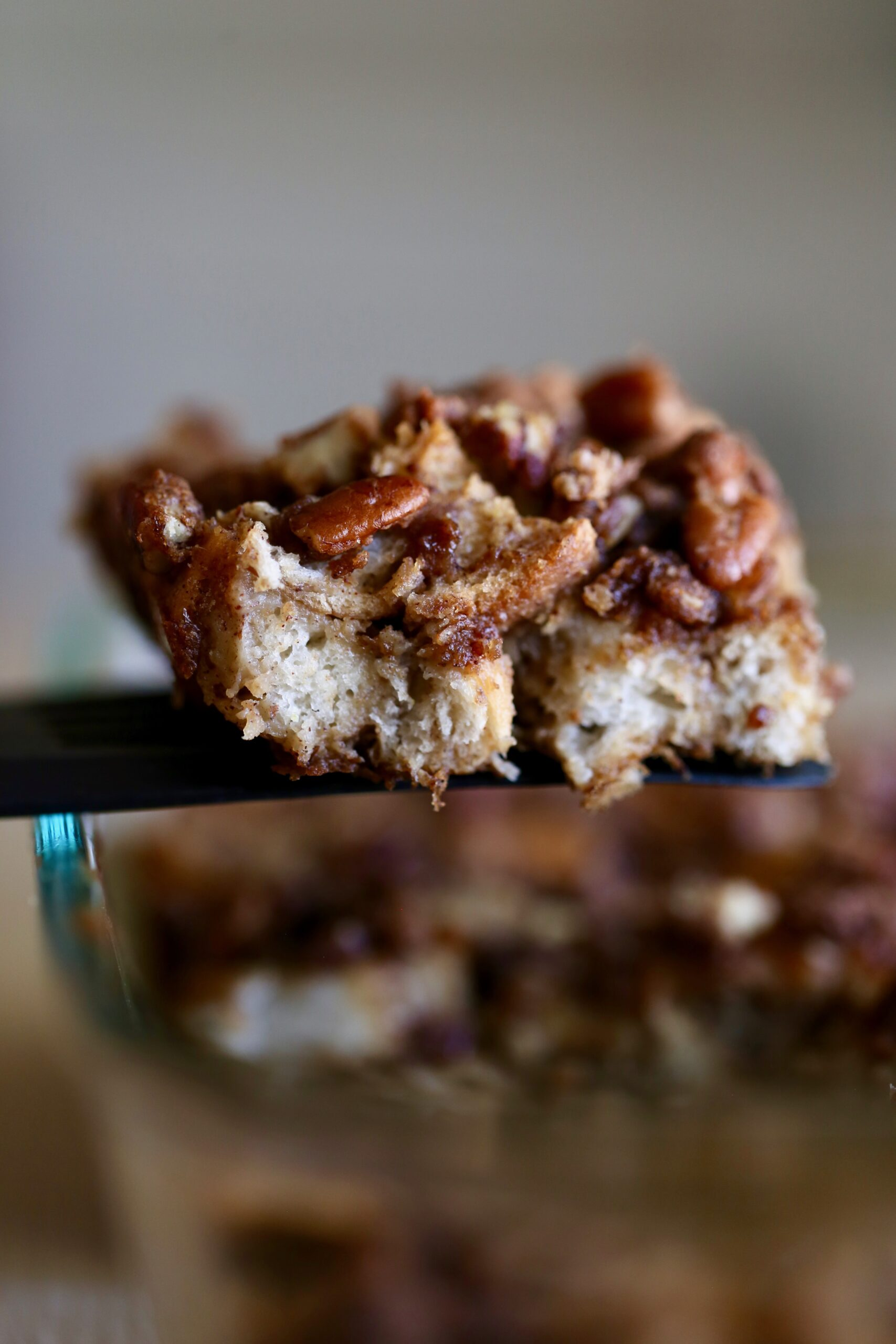 a hearty serving of vegan french toast casserole being lifted out of a casserole dish