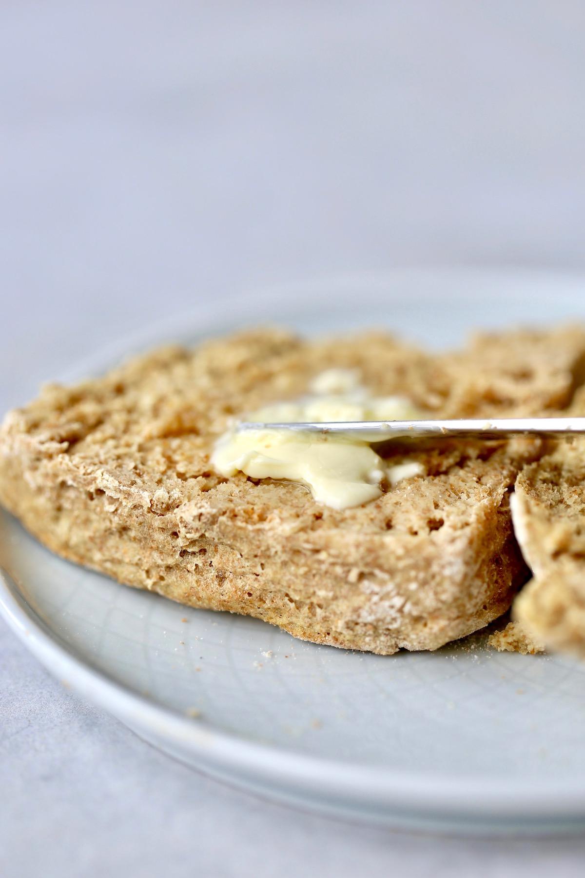 vegan irish soda bread cut in half being smeared with butter