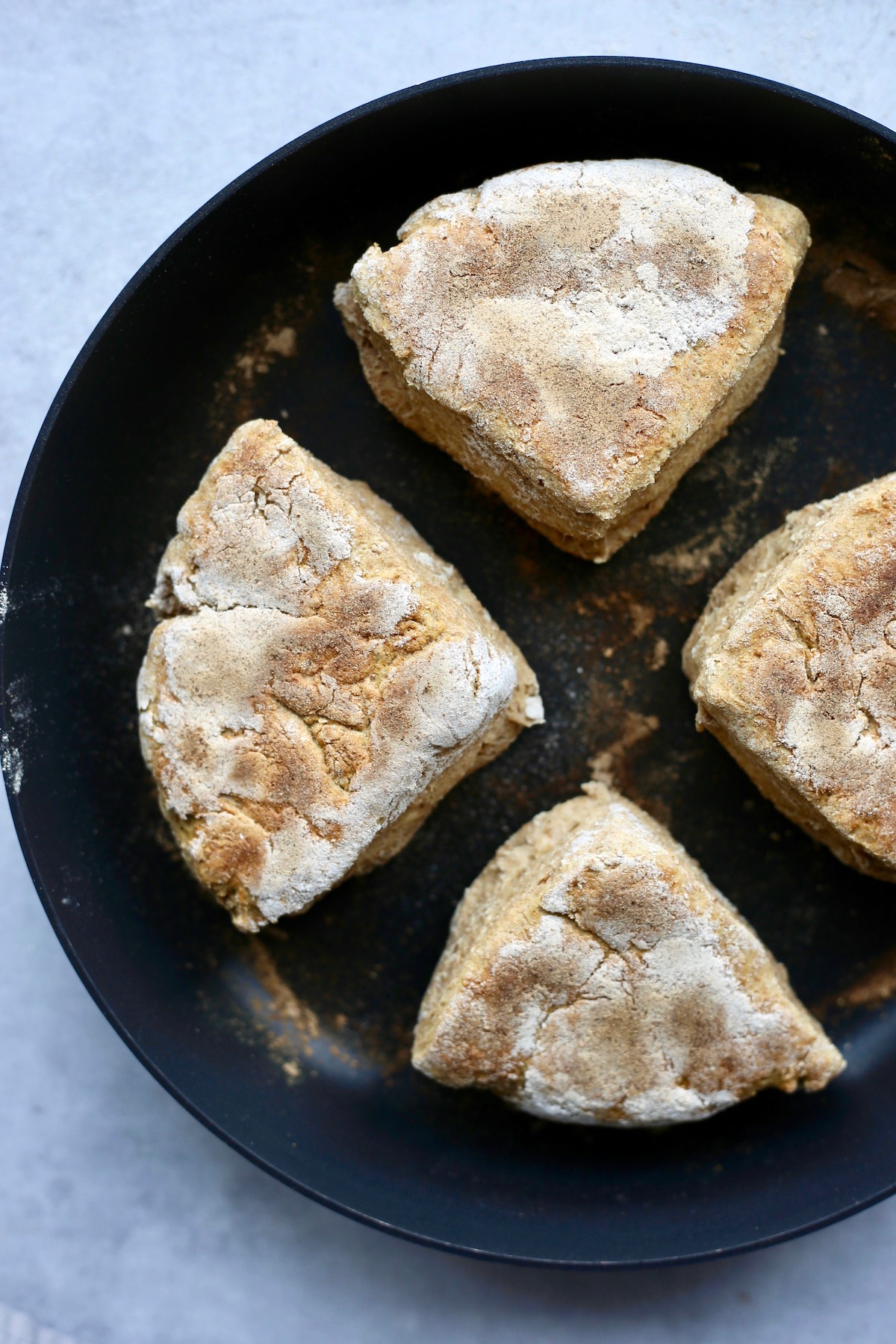 4 vegan Irish soda farls cooking on a hot skillet until golden brown