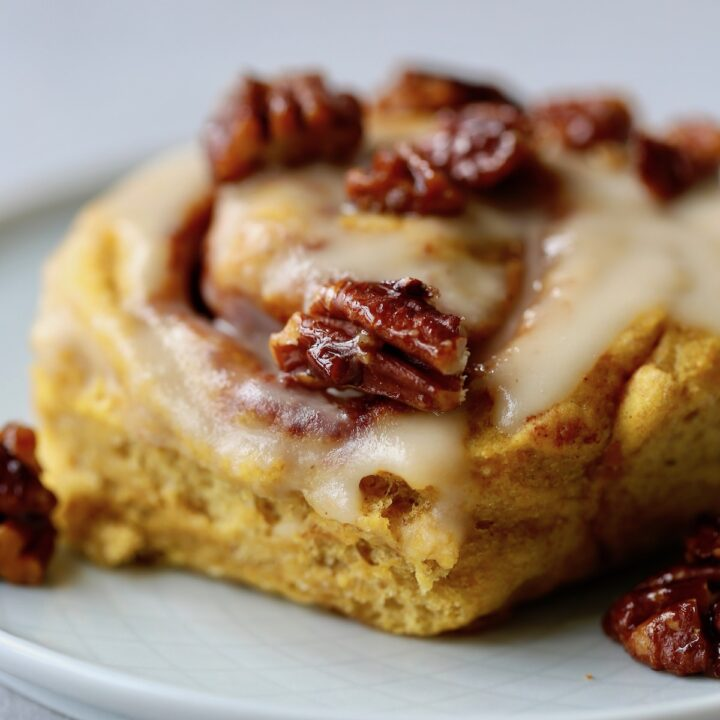 Vegan pumpkin cinnamon rolls topped with candied pecans!