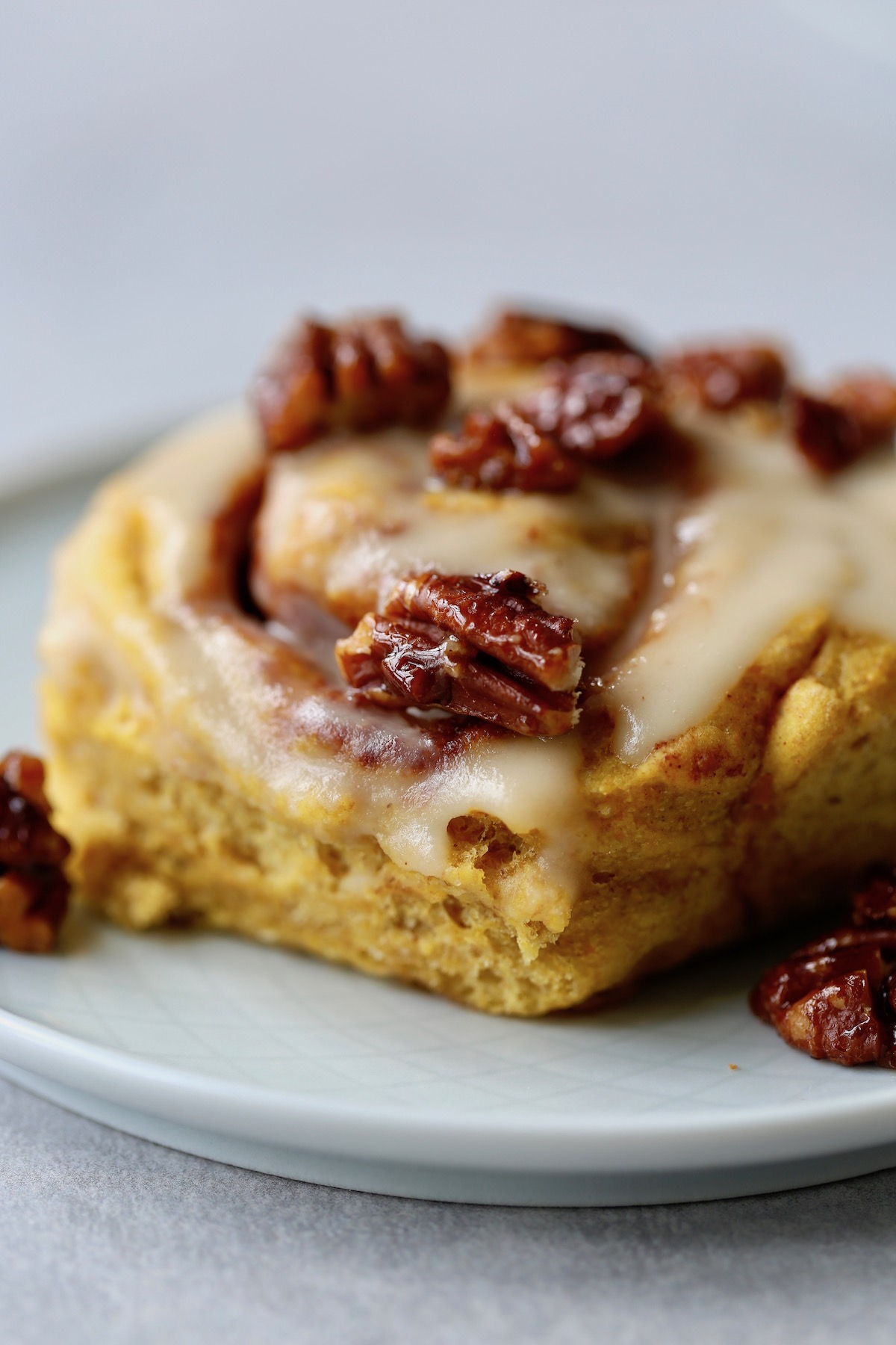glazed pumpkin cinnamon roll topped with candied pecans