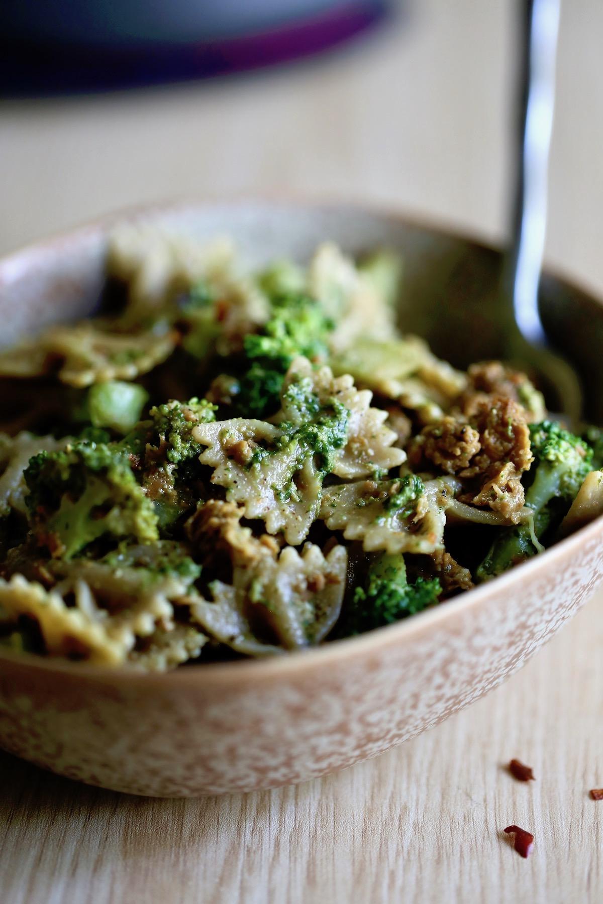 vegan sausage pesto pasta with broccoli piled high in a bowl