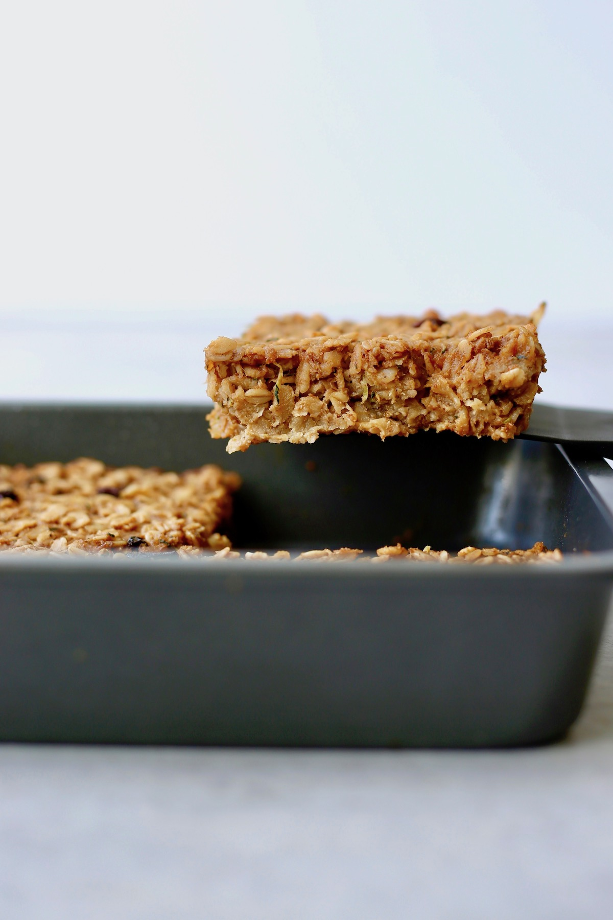 a thick slice of zucchini bread baked oatmeal being lifted out of a baking dish