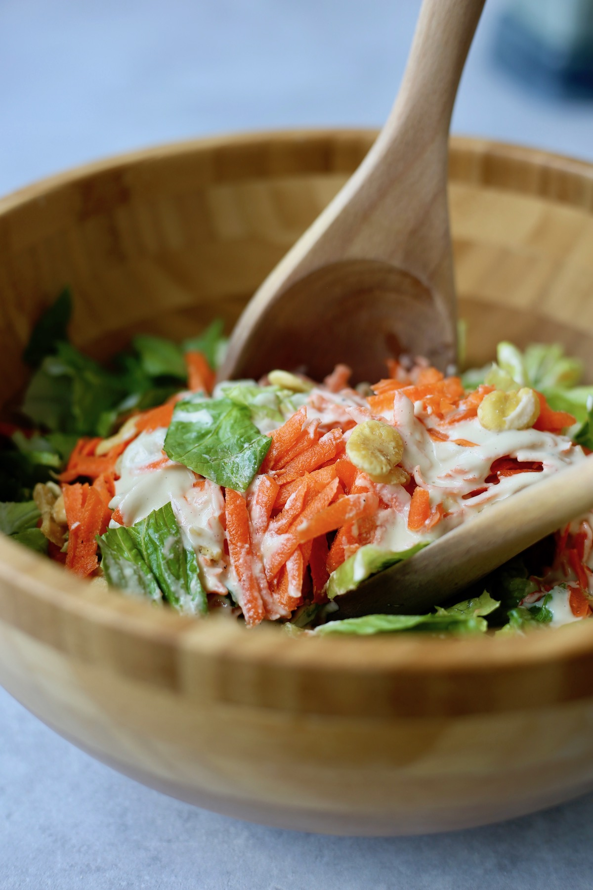 shredded carrots, romaine and vegan Caesar dressing being mixed together in a bowl