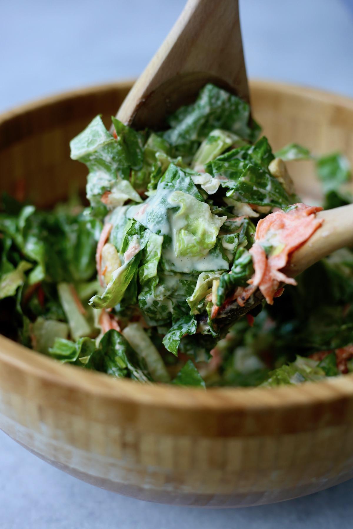 creaming vegan Caesar dressing coating a large spoonful of greens
